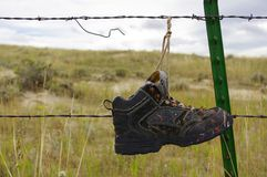 Old shoe hanging from barbed wire fence. Royalty Free Stock Images