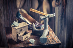 Old shoemaker workplace with tools, leather and shoes Stock Images