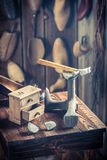 Old shoemaker workplace with tools, shoes and leather Stock Photo