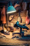 Old shoemaker workplace with tools, shoes to repair. On wooden table royalty free stock images