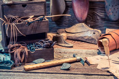 Old shoemaker workshop with brush and shoes Stock Image