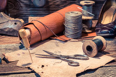 Old shoemaker workshop with tools, shoes and laces. On old wooden table royalty free stock images