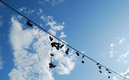 Old shoes. Hanging on cable wire Stock Images