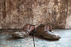 Old shoes. Old dirty brown leather shoes on wooden floor Stock Photo