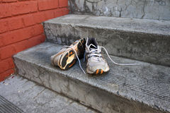 Old Shoes. A pair of old running shoes on cement steps with a red brick wall as a background Royalty Free Stock Photos