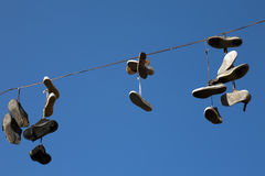 Old shoes in the air. Detail of old shoes hanged in the air Stock Photos
