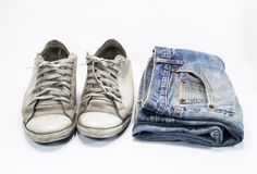 Old shoes and old jeans. Different blue jeans isolated on white background Royalty Free Stock Images