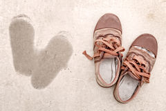 Old shoes on dirty background with footprint beside Royalty Free Stock Photo