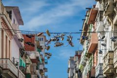 Old Shoes. Hanging shoes. Old shoes hanging in electric wires as seen on the streets of Havana. A bright blue sky as a background stock image