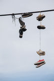 Old shoes hanging on the wire - life change. Street art against blue sky Stock Photography
