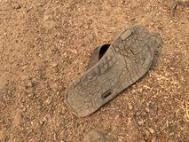 The old shoes on the sand floor were damaged. The soles of the shoes were worn by walking for a long time. Ago stock photography