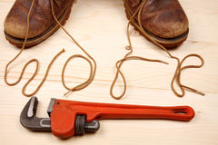 Old shoes with shoelaces with red adjustable wrench Royalty Free Stock Photo
