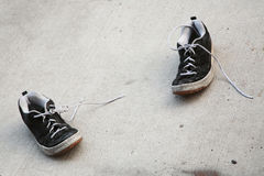 Old shoes in street. Keds shoes old used string street dirty Stock Photos