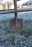 An old shovel on the frozen grass Royalty Free Stock Images