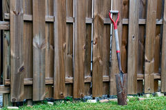 Old shovel leaning against fence Stock Images