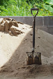 Old shovel in sand for construction Stock Photo