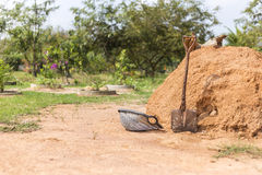 Old shovels and buckets beside a pile. Stock Photo