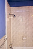 Old shower and tub. Tiled wall of bathroom showing showerhead, tub faucet, towel rack and blue walls stock images