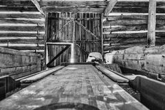 Old shuffleboard game and snowmobile in a barn Stock Photos