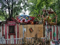 Old shutdown funhouse with scary clown. Over fence Royalty Free Stock Photography