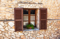 Old Shutter windows with a pot of flowers. Mallorca. Mediterrane Royalty Free Stock Photos