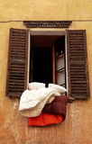 Old shutters window with bedclothes, Italy Stock Image