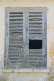 Old shutters on window, Sami, kefalonia,Greece. Old shutters with big hole on window, Sami, kefalonia,Greece Royalty Free Stock Image