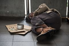 Old sick beggar or Homeless dirty man sleep on footpath with donate bowl, dollar bill, coin, paper cardboard with help text. Feeling cold during winter with stock photography
