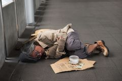Old sick beggar or Homeless man in city. Old sick beggar or Homeless dirty man sleeping on footpath with guitar, donate bowl, paper cardboard with help text royalty free stock photos