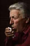 Old sick man. In a shirt on a brick background Royalty Free Stock Photography