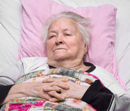 Old sick pensive woman. Lying at bed Stock Photo