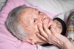 Old sick pensive woman. Lying at bed Royalty Free Stock Photography