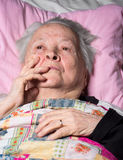 Old sick pensive woman. Lying at bed Royalty Free Stock Images