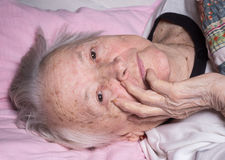 Old sick pensive woman. Lying at bed at home Stock Photo
