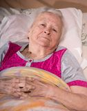 Old sick pensive woman. Lying in bed at home Stock Photography