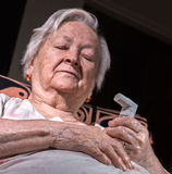 Old sick woman with asthma inhaler Stock Images