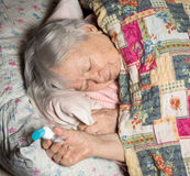 Old sick woman with asthma inhaler Stock Photography