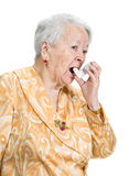 Old sick woman with asthma inhaler. Posing in studio on a white background Royalty Free Stock Photo