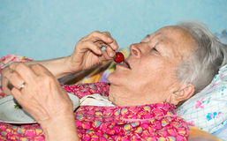 Old sick woman eating strawberry Stock Image