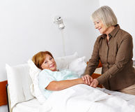 Old sick woman getting visitor Royalty Free Stock Image