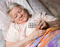 Old sick woman. Lying at bed, holding the medicine in hands Stock Images