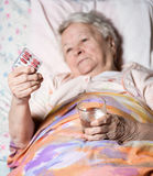 Old sick woman. Lying in bed, holding the medicine in hands Royalty Free Stock Image