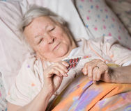 Old sick woman. Lying in bed, holding the medicine in hands Royalty Free Stock Photos