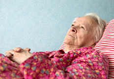 Old  sick woman lying at bed Stock Image
