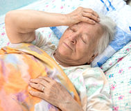 Old  sick woman lying at bed Stock Photo
