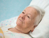 Old  sick woman lying at bed Royalty Free Stock Images