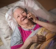 Old sick woman lying in bed and using smart phone Stock Photography