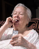 Old sick woman. Taking pill at home Stock Images