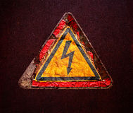 Old sign of high voltage on  rusty metal surface Stock Photography