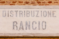 Old sign ration-distribution written in  italian language. Sign made of cement indicating the writing ration-distribution  on a bricks wall Stock Images